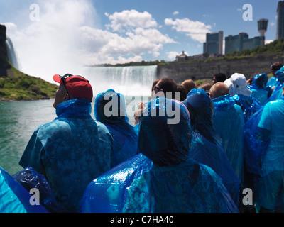 People in blue rain coats on Niagara Falls Maid of the Mist boat ride - Stock Photo