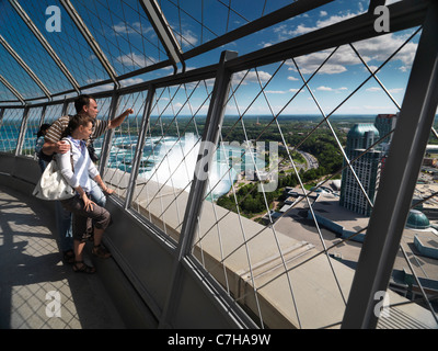Young tourist couple enjoying view from Skylon tower at Niagara Falls, Ontario, Canada. - Stock Photo
