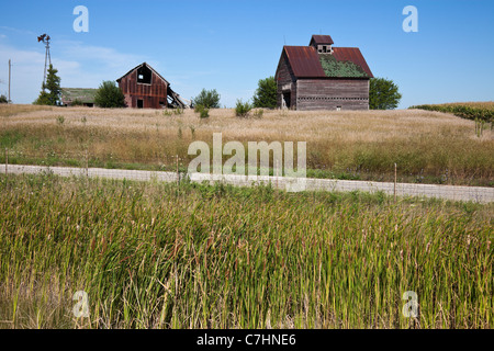 Old farm buildings in the middle of field - Stock Photo