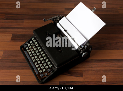 old portable typewriter with blank paper on the floor - Stock Photo
