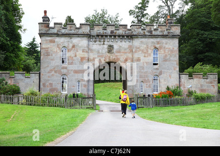 A mother and father with their two children walking by the gate house or gatehouse  at Cholmondeley Castle Cheshire, - Stock Photo