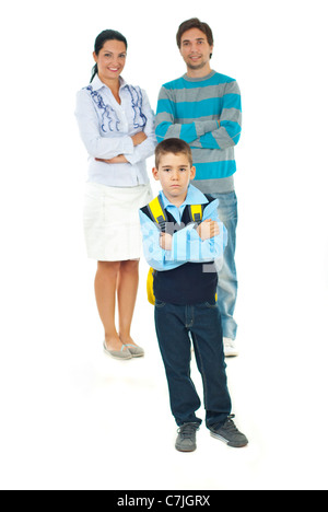 Sad schoolboy standing with arms crossed in front of smiling parents in first day of school against white background - Stock Photo