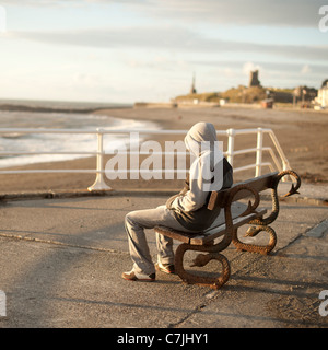A young man wearing a hoodie sitting alone on a seaside bench, Aberystwyth Wales UK - Stock Photo