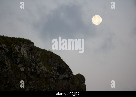 full moon setting over rocky shoreline benone strand beach county derry londonderry northern ireland uk - Stock Photo