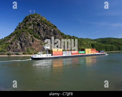 Large barge carrying container freight passes Loreley rock on River Rhine in Germany - Stock Photo