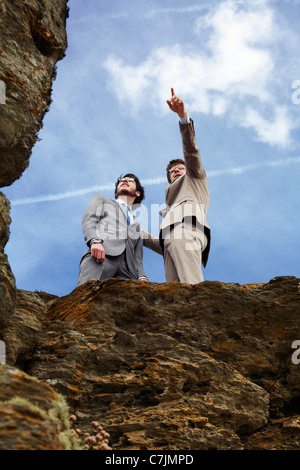 Businessmen standing on cliff edge - Stock Photo