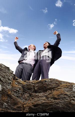 Businessmen cheering on cliff edge - Stock Photo