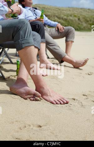 Businessmen's bare feet on beach - Stock Photo