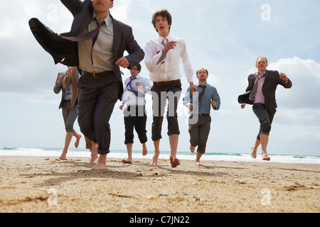 Businessmen running on beach - Stock Photo