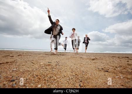 Businessmen running on beach - Stock Photo