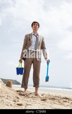 Businessman building sand castle - Stock Photo
