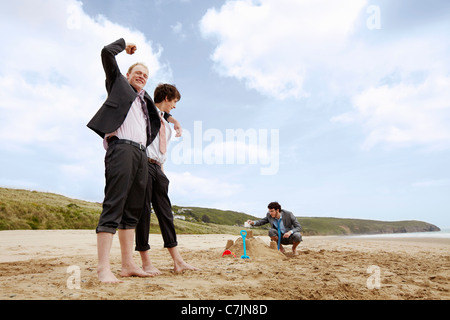 Businessmen building sand castle - Stock Photo