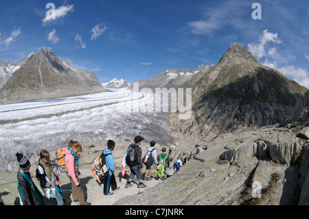 Switzerland, Valais, Western Europe,, Aletsch Glacier (UNESCO world heritage site). Teenage hikers on the panorama - Stock Photo