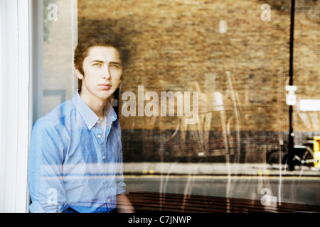 Teenage boy looking out window - Stock Photo
