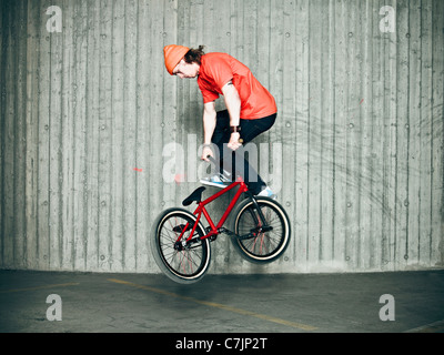 Man doing tricks on bmx bike indoors - Stock Photo