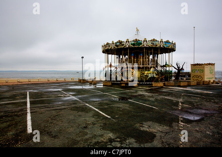 Abandoned carousel in parking lot - Stock Photo