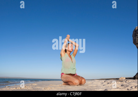 Woman in bikini kneeling on beach - Stock Photo