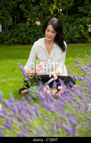 Woman with basket of flowers in backyard - Stock Photo