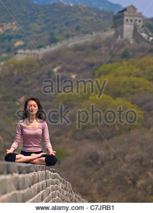 Woman meditating on Great Wall of China - Stock Photo