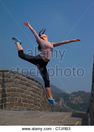 Woman jumping on Great Wall of China - Stock Photo