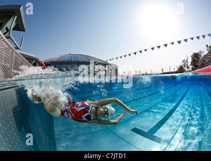 A female swimmer training in an open air Olympic swimming pool (France). Underwater view. - Stock Photo