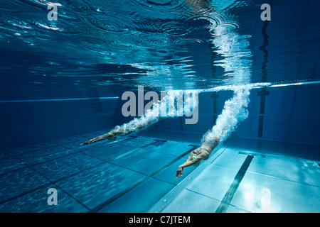 Olympic Swimming Underwater female swimmers diving into swimming pool for competitive race