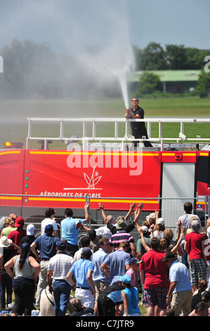 French Firefighters cooling crowd during  extremely hot weather, at Le Bourget airshow 2011 - Stock Photo