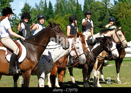Six young horses and riders stand in a row together before a show jumping competition at a horse show in Ontario, - Stock Photo
