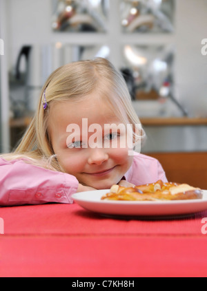 Young girl, 6, sitting at a table - Stock Photo