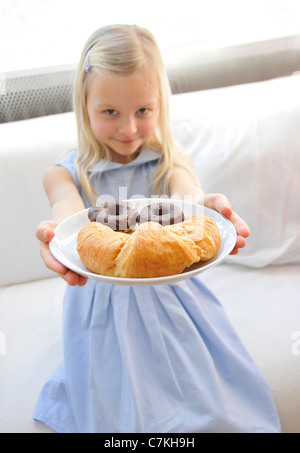 Young girl, 6, with a blue dress presenting a plate with chocolate donuts and a croissant - Stock Photo