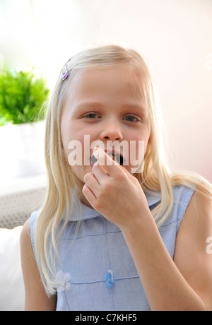 Young girl, 6, with a blue dress eating a donut - Stock Photo