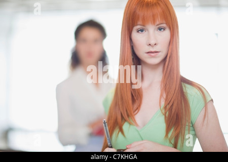 Red-haired woman holding pen - Stock Photo