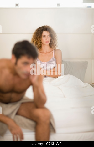 Couple arguing in bedroom - Stock Photo