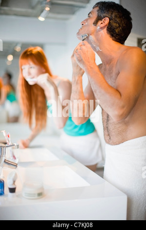 Couple brushing teeth and shaving - Stock Photo