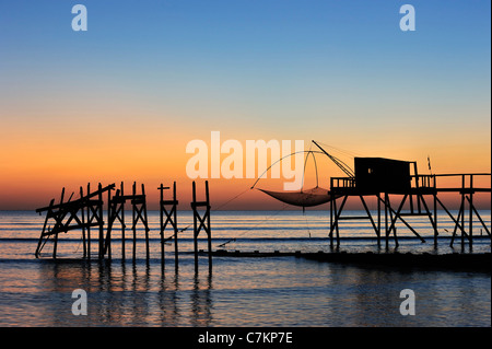 Traditional carrelet fishing hut with lift net on the beach at sea at sunset, Loire-Atlantique, Pays de la Loire, - Stock Photo