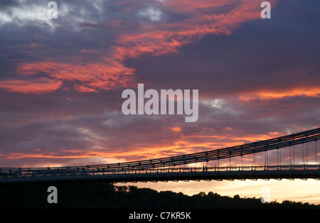 Two silhouetted figures walking over the Clifton Suspension Bridge in Bristol at sunset - Stock Photo