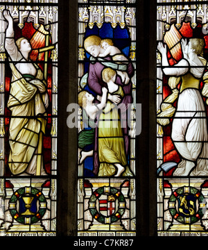 Fine stained glass window triptych idealising maternal virtues in the church of St Morwenna and St John the Baptist - Stock Photo