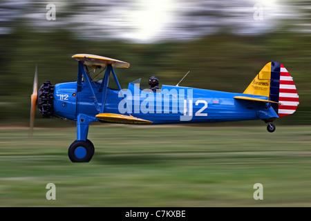 Boeing Stearman biplane taking off - Stock Photo