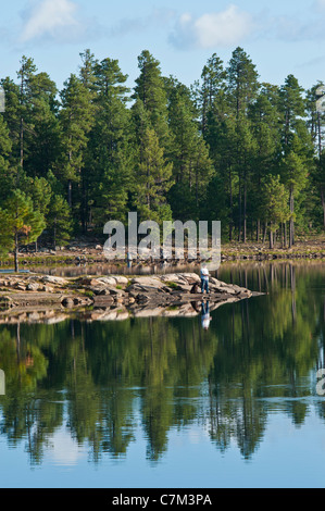 A man and his best friend doing some fishing before breakfast on Willow Springs Lake, Arizona. - Stock Photo