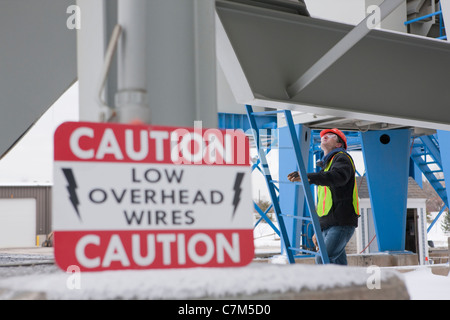 Warning sign at an industrial plant with an engineer climbing a ladder - Stock Photo