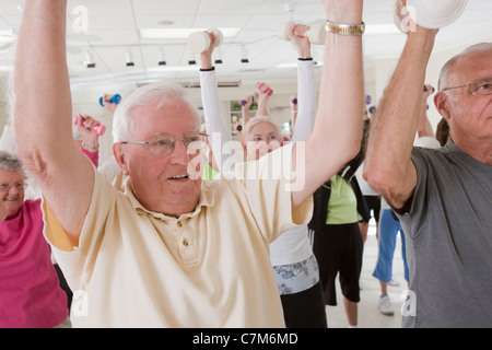 People exercising with dumbbells in a health club - Stock Photo