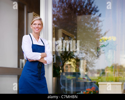 Portrait of beautiful caucasian girl self-employed in flower shop, smiling and looking away. Horizontal shape, waist - Stock Photo