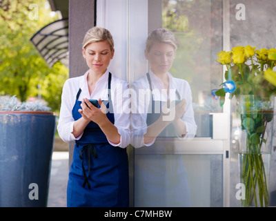 Portrait of beautiful caucasian girl self-employed in flower shop, smiling and using mobile phone. Horizontal shape, - Stock Photo