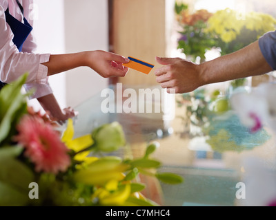Young woman working as florist giving credit card to customer after purchase. Horizontal shape, closeup - Stock Photo