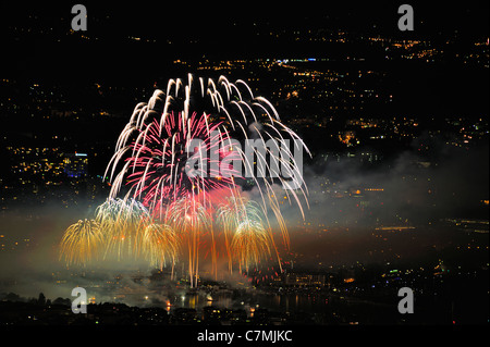 Firework burst in the night sky over Geneva. Taken from a high point (the Saleve mountain) looking down on town - Stock Photo