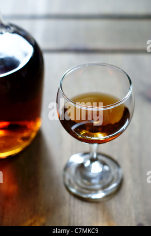 A bottle of alcohol or liquor and a measure in a glass equivalent to one unit of alcohol - Stock Photo