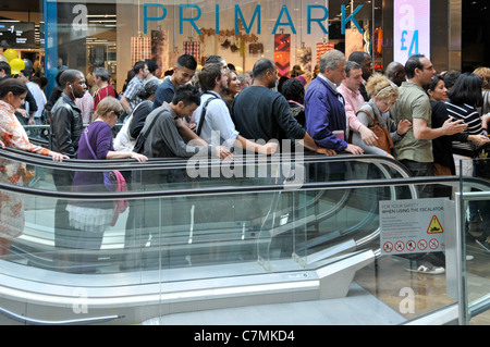 Group of people shoppers on busy indoor down escalator Westfield shopping centre mall outside Primark clothing store - Stock Photo