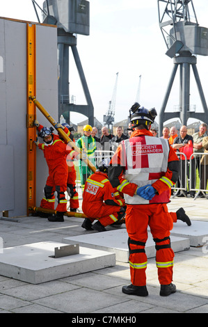 Urban Search & Rescue Fire Brigade teams competing & being assessed at UK Rescue Challenge event erecting temp shoring - Stock Photo