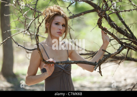 Portrait of young beautiful auburn haired woman in the forest, standing among bare tree branches. - Stock Photo