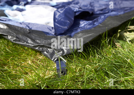 putting in taking out tent pegs putting up taking down a tent in a field - Stock Photo